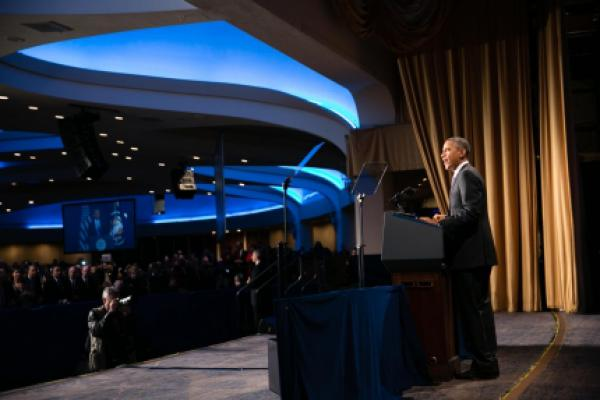 President Obama standing at a podium, speaking to Senior Executive Service employees